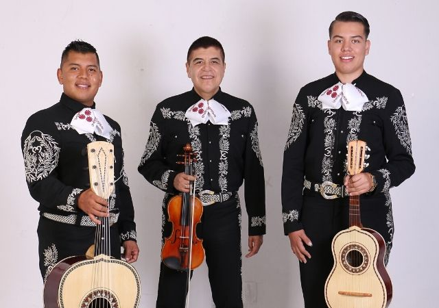 Trio Jalisco en la Piel posing with their guitars and violin
