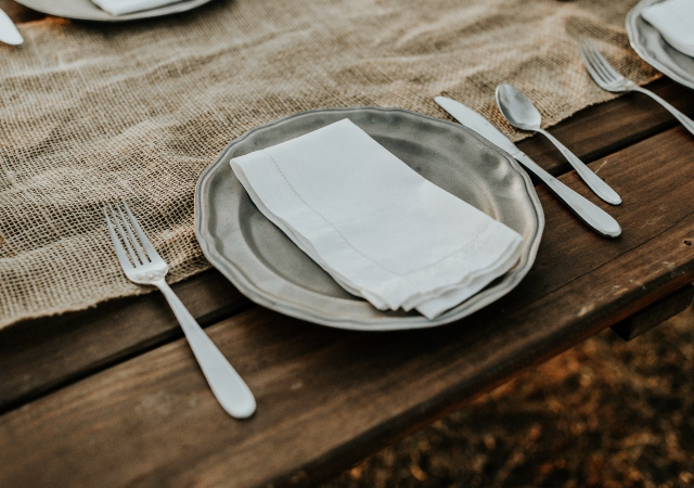 a wooden table with an empty place setting of a silver plate and utensils