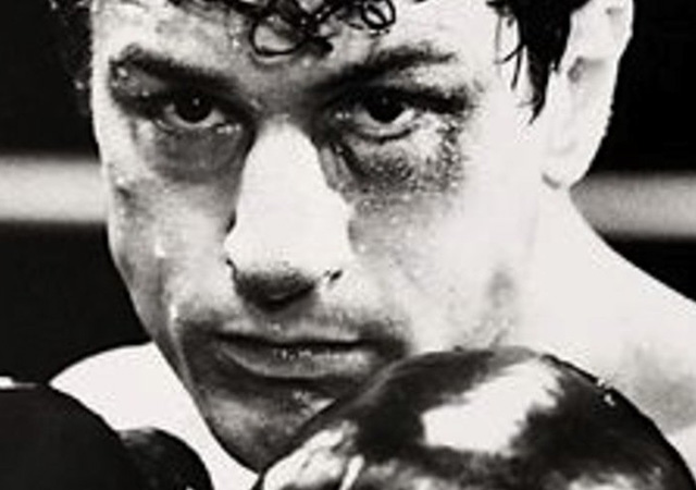 Move still of a closeup of Robert De Niro's character in boxing gloves.