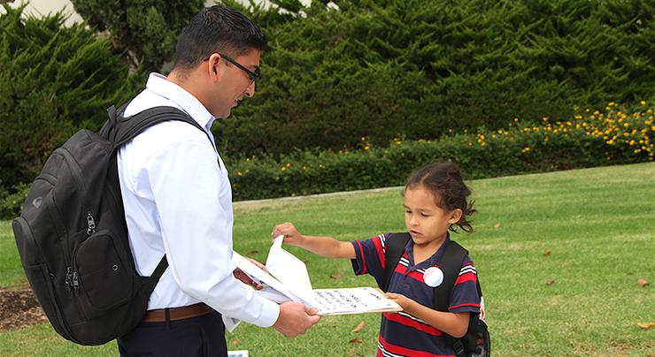 Frank Garcia, left, is asked by a High Tech Elementary School student if he's registered to vote in the upcoming election and if he'll sign a pledge to do so.