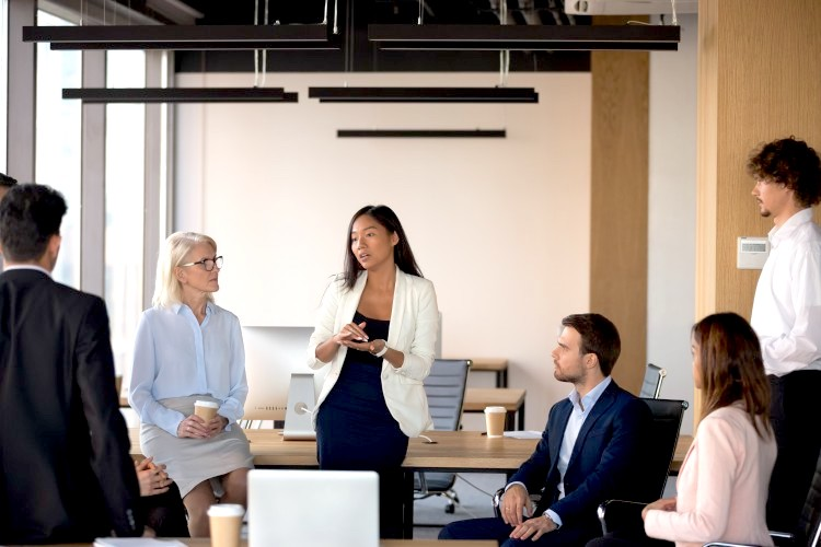 A group of employees listen to their marketing director who is leaning against a table