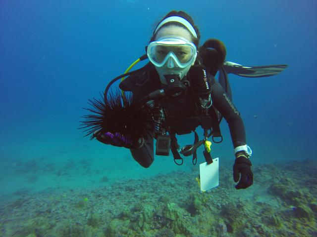 Anela is scooba diving and holding a sea urchin.