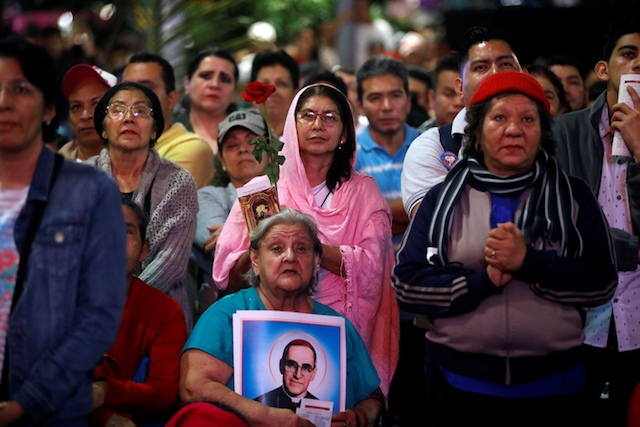 Crowd holding photos of St. Oscar Romero at a rally