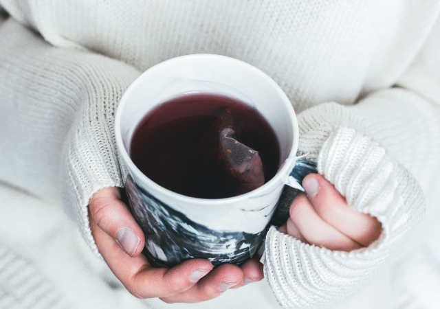 hands holding hot cup of tea