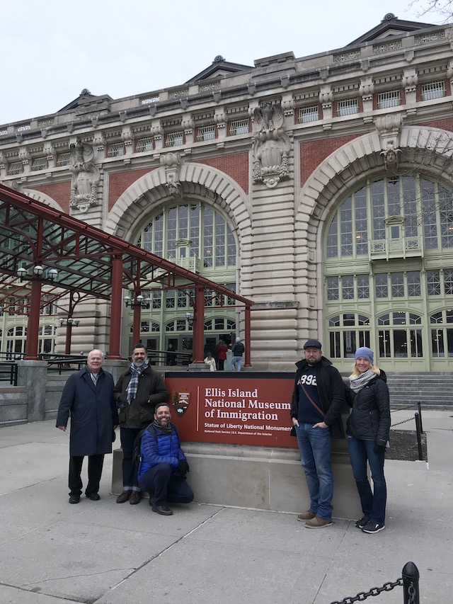 faculty standing in front of Ellis Island sign on Ellis Island