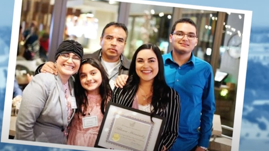 Blanca Hernandez smiles with her family while holding her USD business degree