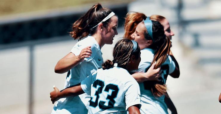 The USD women's soccer team celebrates with hugs after scoring a goal in a 4-0 win over Holy Cross on Sunday. The Toreros are 2-0 after a pair of weekend games.