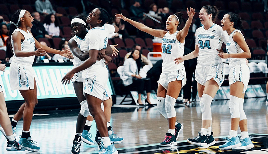 The USD women's basketball team celebrates after winning its UCU West Coast Conference Tournament semifinal over Pepperdine on Monday.  USD and Portland meet for the WCC title at 1 p.m. Tuesday.