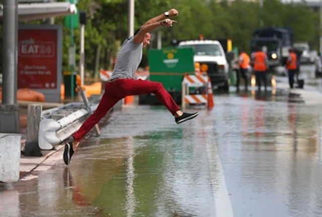 Michel Rodriguez tries to jump to a shallow spot as he crosses a flooded street that was caused by the combination of the lunar orbit which caused seasonal high tides