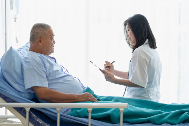 An Asian doctor visits with an elderly Asian patient in a hospital room.