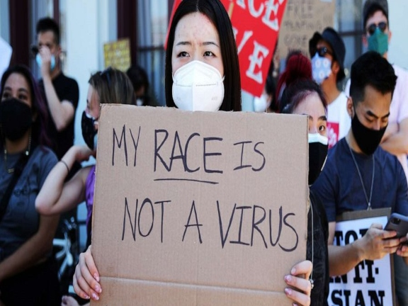 Asian women holding protest sign (alt) *