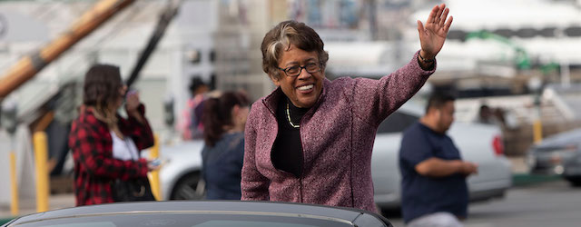 Dr. Constance Carroll waving from a car in a parade