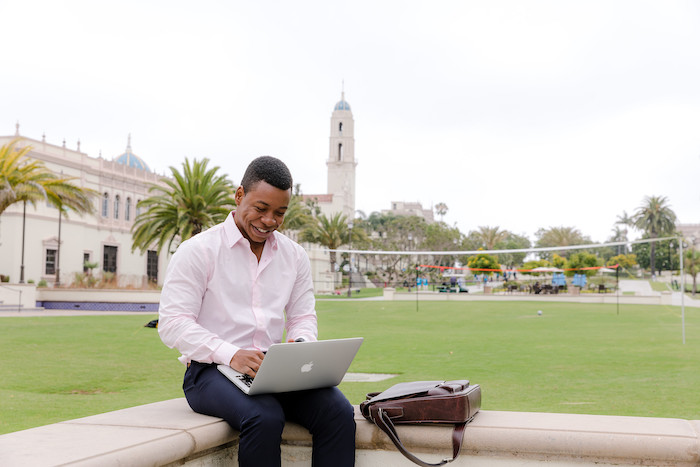 A student smiles and works on his laptop on campus at the University of San Diego