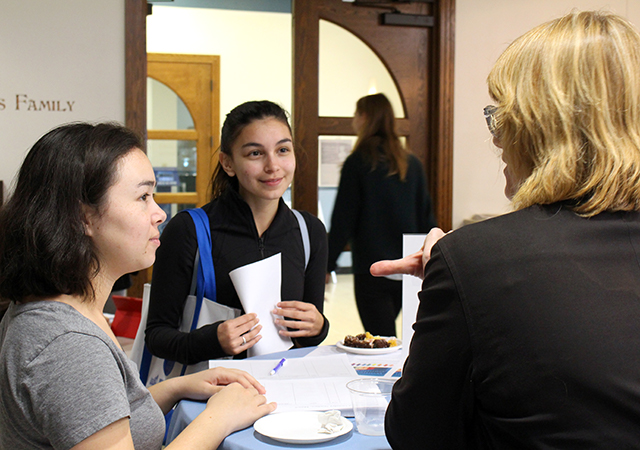 Photo of two students talking and networking with a professional