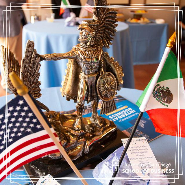 A small statue of an Aztec man sits beside an American flag and Mexican flag on a table
