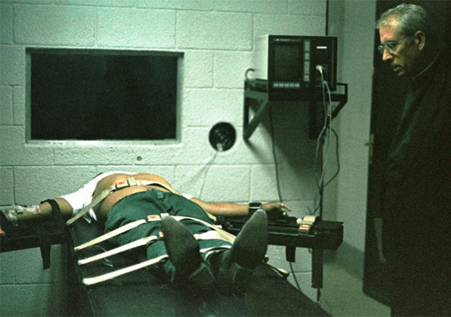 A man who is sentenced to death is lying on a table with his arms spread apart and a priest is looking down at him.