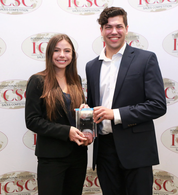 Two of USD's sales team members pose with their first place trophy at the International Collegiate Sales Competition