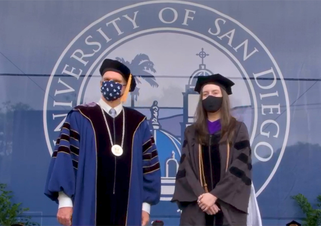 Photo of USD law graduate with President Harris during Commencement