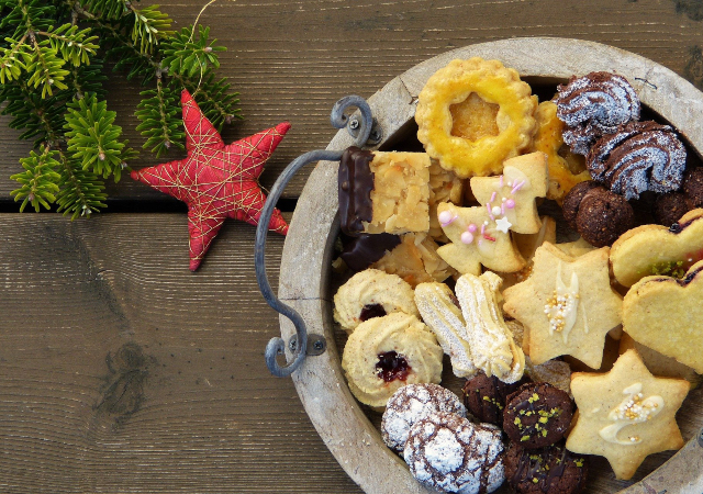 a plate of various cookies on a wooden table with a red star and green pine tree cuttings