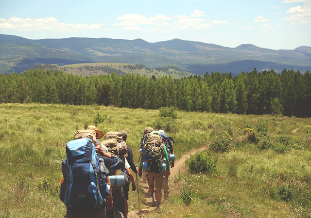 People backpacking through nature