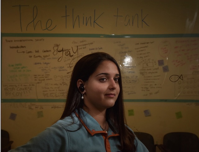Ela Gokcigdem, a 17-year-old climate activist in Arlington posing in front of a lesson plan