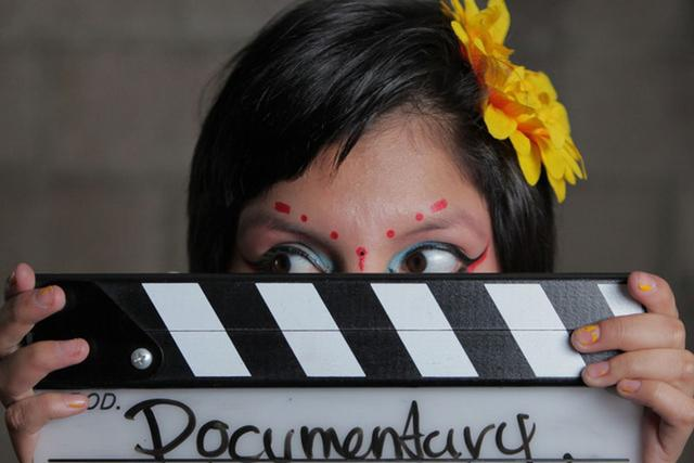 young girl's face with colorful makeup hiding behind movie marker