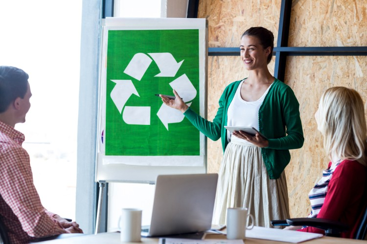 A woman at a white board presents a recycling initiative.