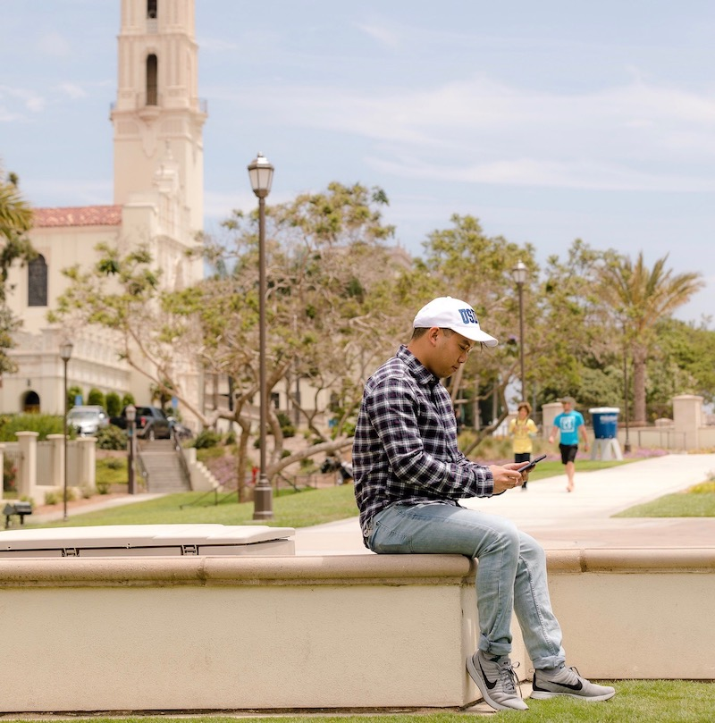 University of San Diego student sits on campus wall