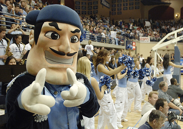 Mascot Diego Torero facing the camera with cheerleaders behind him.