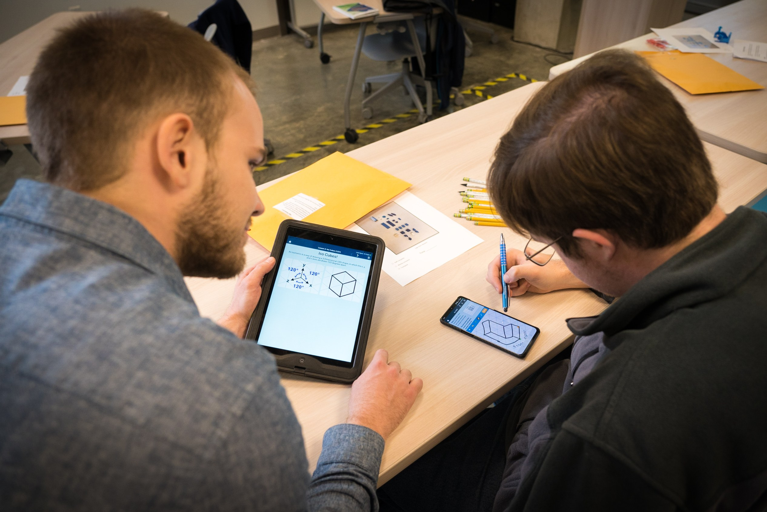 A photo of two people working on a phone and ipad