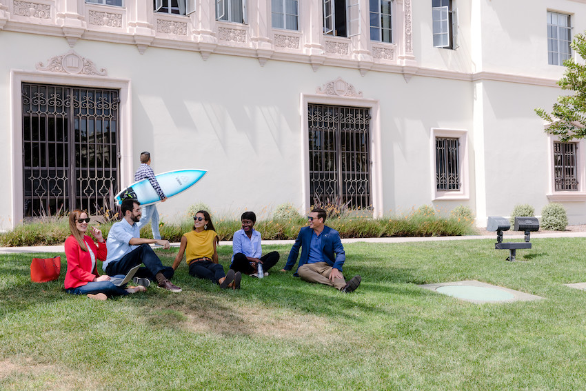 A diverse group of students sit on a lawn at the University of San Diego