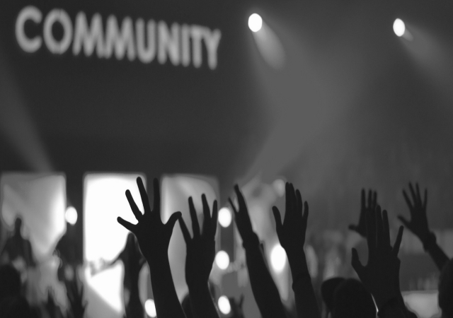 black and white photo of crowd of people reaching out to a sign that reads community