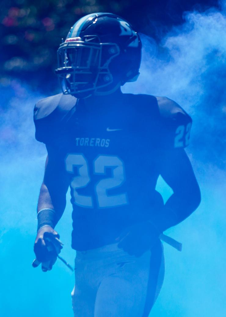 Daniel Tolbert runs through blue smoke