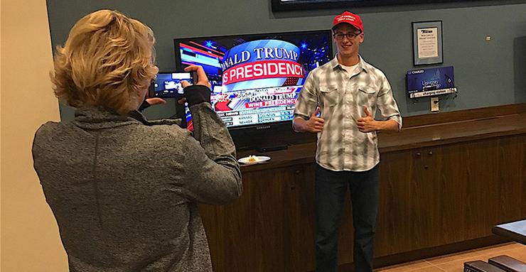 A USD student has a friend take his picture in Frank's Lounge to commemorate the announcement that Donald Trump has won the 2016 presidential election.