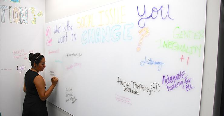 Bianca Alvarado, a student in the new MA in Social Innovation degree program in the Kroc School, answers a question on the wall of the new Wasson Social Innovation Lab space at USD.