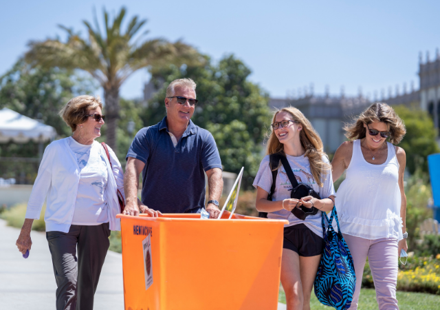 Family members help a first-year student move in to her residence hall.