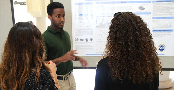 USD junior Daniel Ghebreigziabher discusses his NSF REU summer research project during a poster presentation session on August 10.