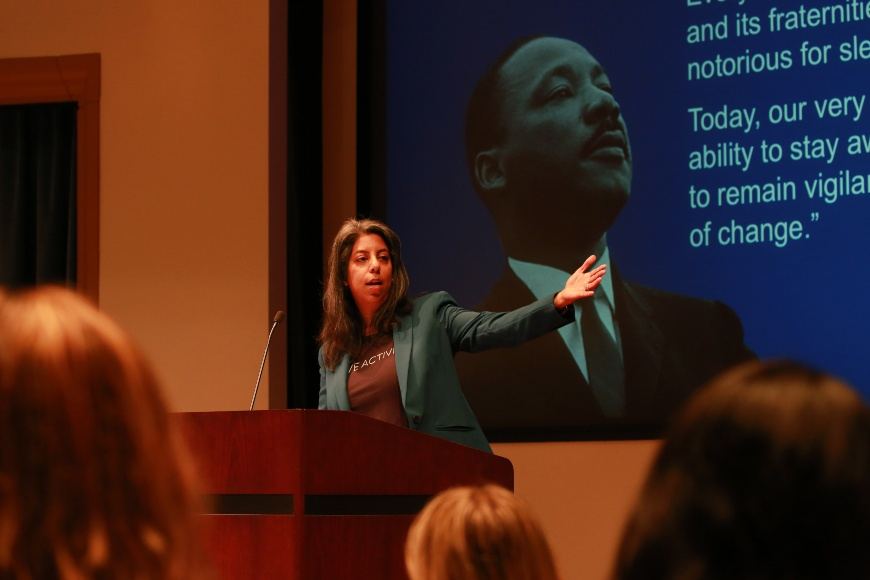 Bina M. Patel speaking in an auditorium full of people at the Governance Symposium with a Martin Luther King Jr. quote behind her on the screen
