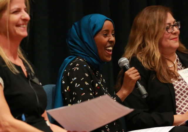 three women panel speakers laughing and smiling