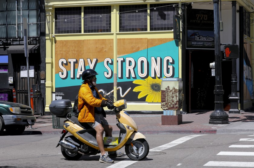 A man riding his scooter waits at the traffic signal on the corner of Fifth Avenue and F Street,(Nelvin C. Cepeda/The San Diego Union-Tribune)