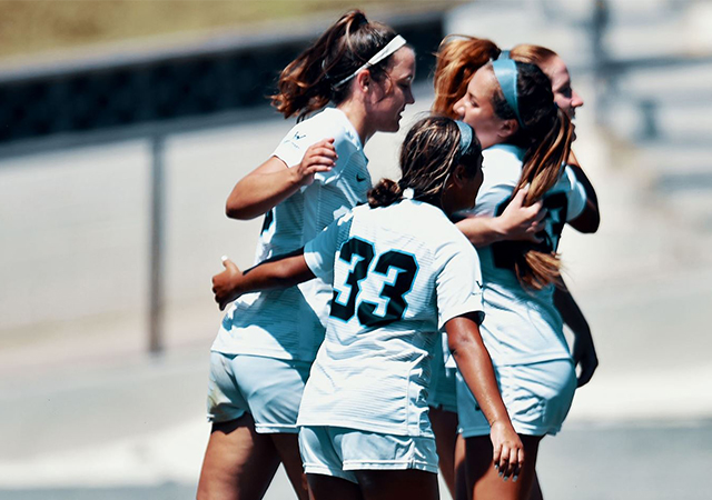 Members of the USD women's soccer team celebrate after a goal in Sunday's 4-0 win over Holy Cross