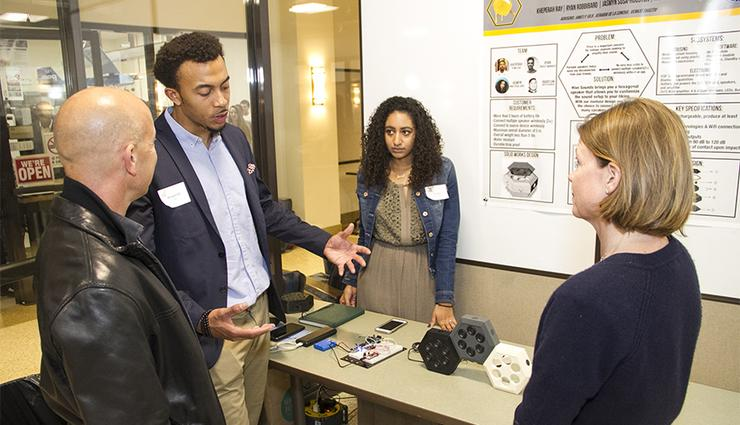 Electrical Engineering student Kheperah Ray, second from left, discusses his entrepreneurial product, HIVE Soundz, during the Engineering and Computing Showcase in Spring 2018.