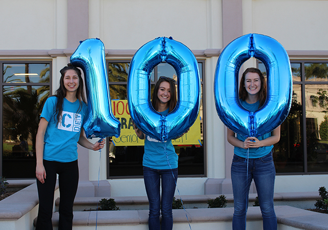 USD students holding up 100 in balloons for 100 Days Til Graduation countdown