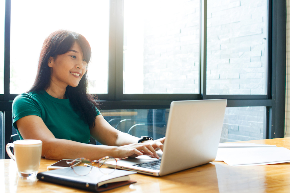 An Asian woman sits at a desk working on a laptop.