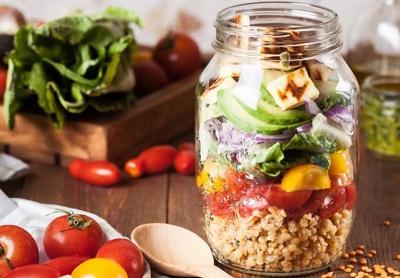 Ingredients for a salad inside of a jar.