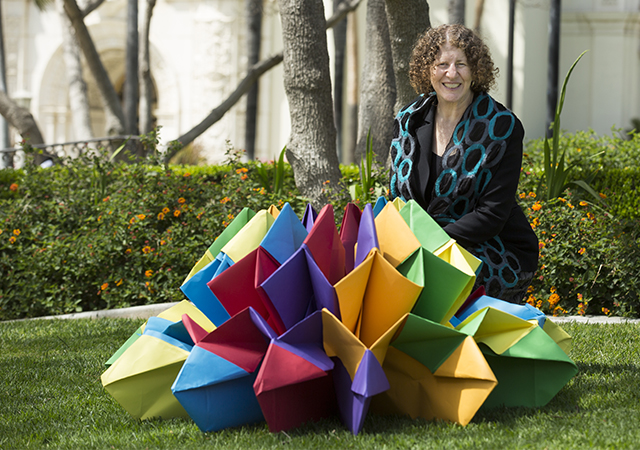 Perla Myers, part of Project VisMo, poses with a large origami piece