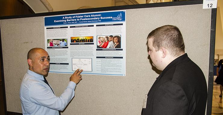 Pedro Flores, left, a first-year PhD student in the School of Leadership and Education Sciences, shares his research study on foster care alumni and barriers to postsecondary success.