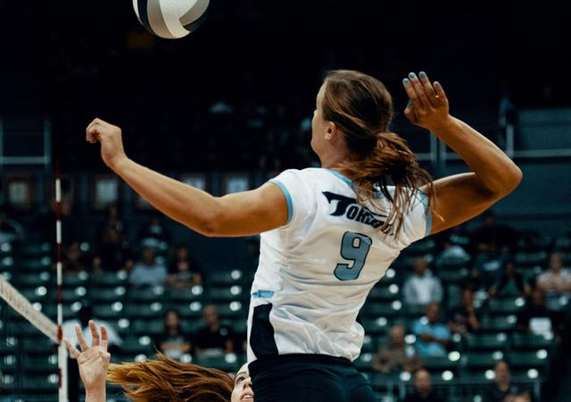 USD volleyball's Megan Jacobsen sends a ball over the net.