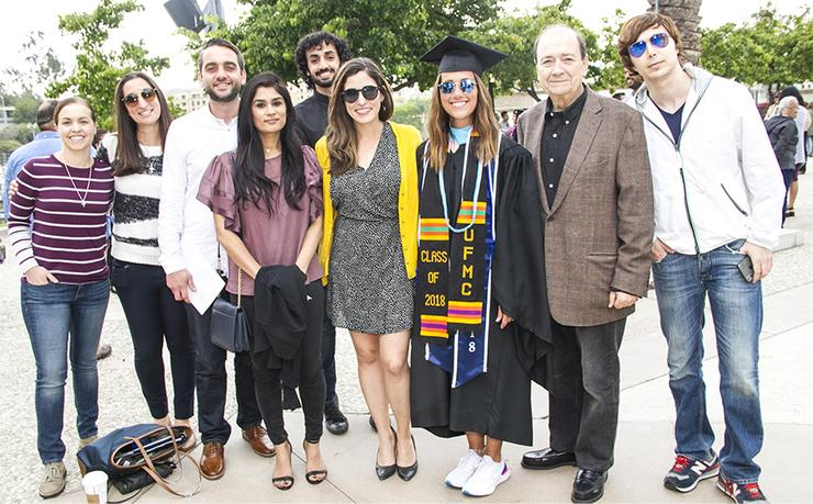 Rama Sabano, third from right, is flanked by colleagues, friends and family following her graduation from SOLES' Master's in Higher Education Leadership.