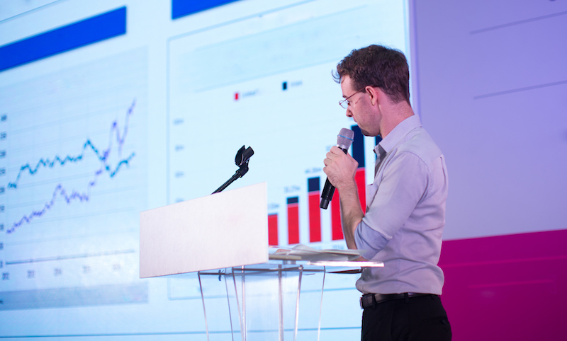 Man with microphone stands on stage in front of line and bar graphs.